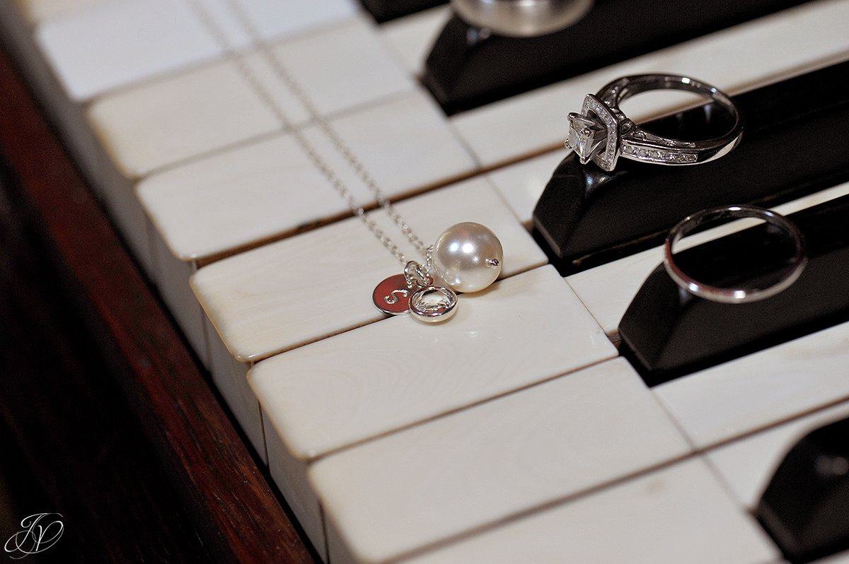photo of wedding jewelry on piano