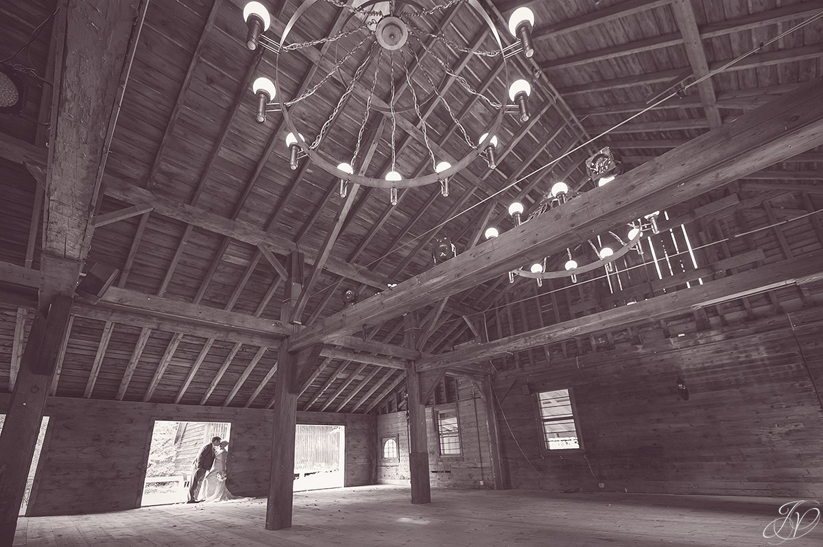 unique black and white photo of bride and groom in barn