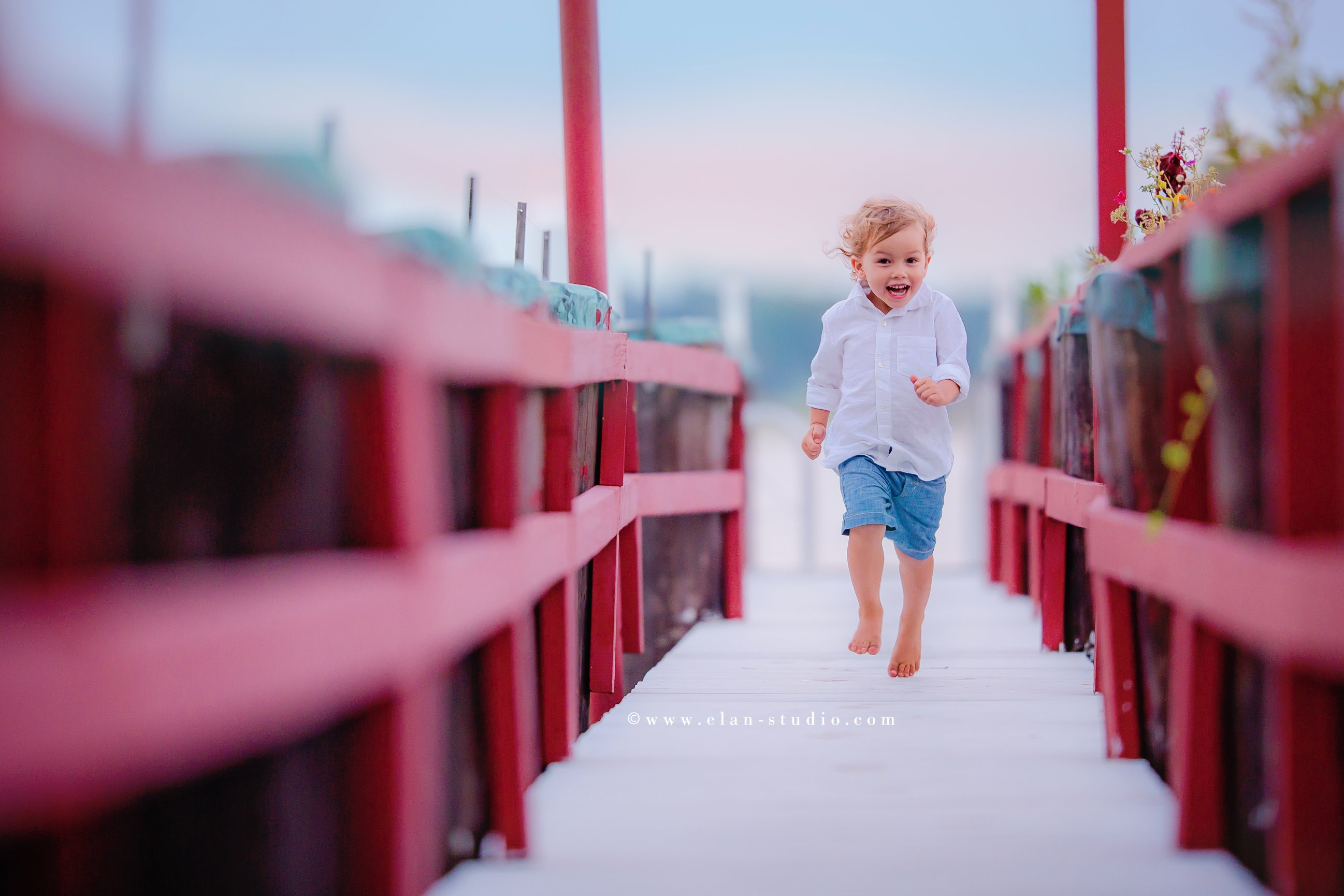 little boy in white button-down shirt and blue shorts running on red dock
