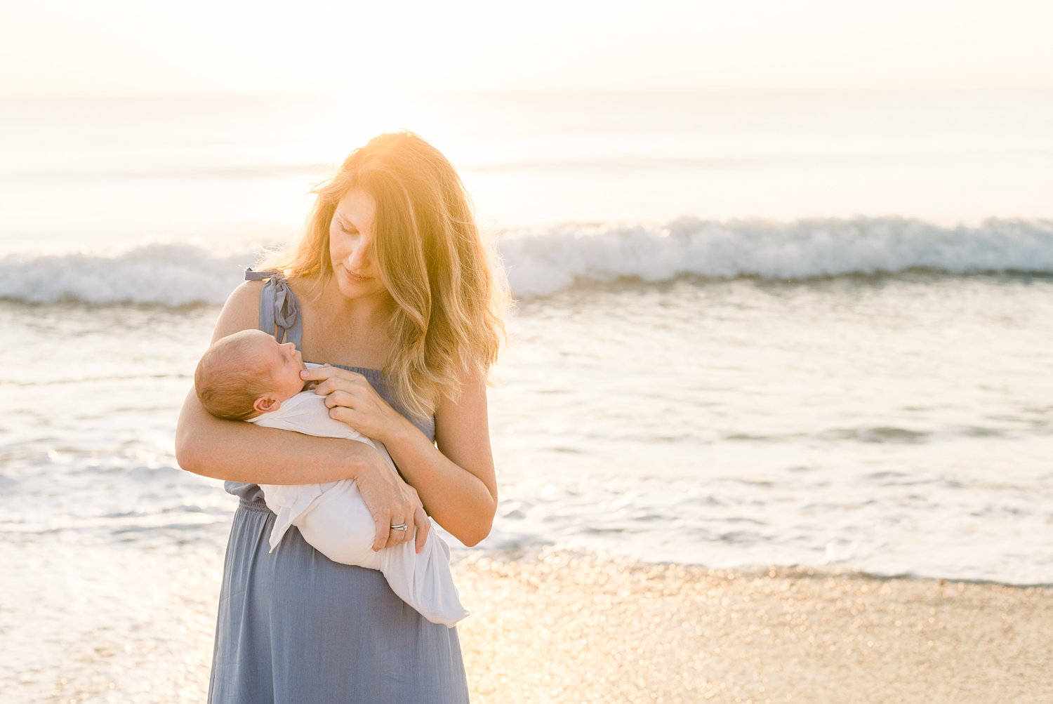 mom wearing a cornflower blue dress, she is holding her newborn baby, the sun is rising in the background