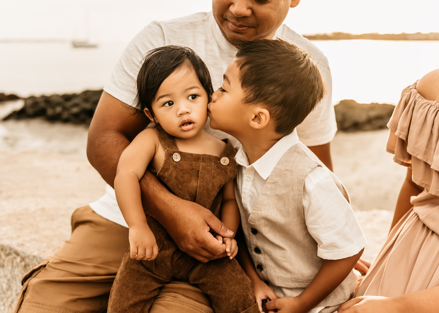 father holding his 2 young boys, one brother is kissing the other brother's cheek, mom's dress is peeking from the right side of the image