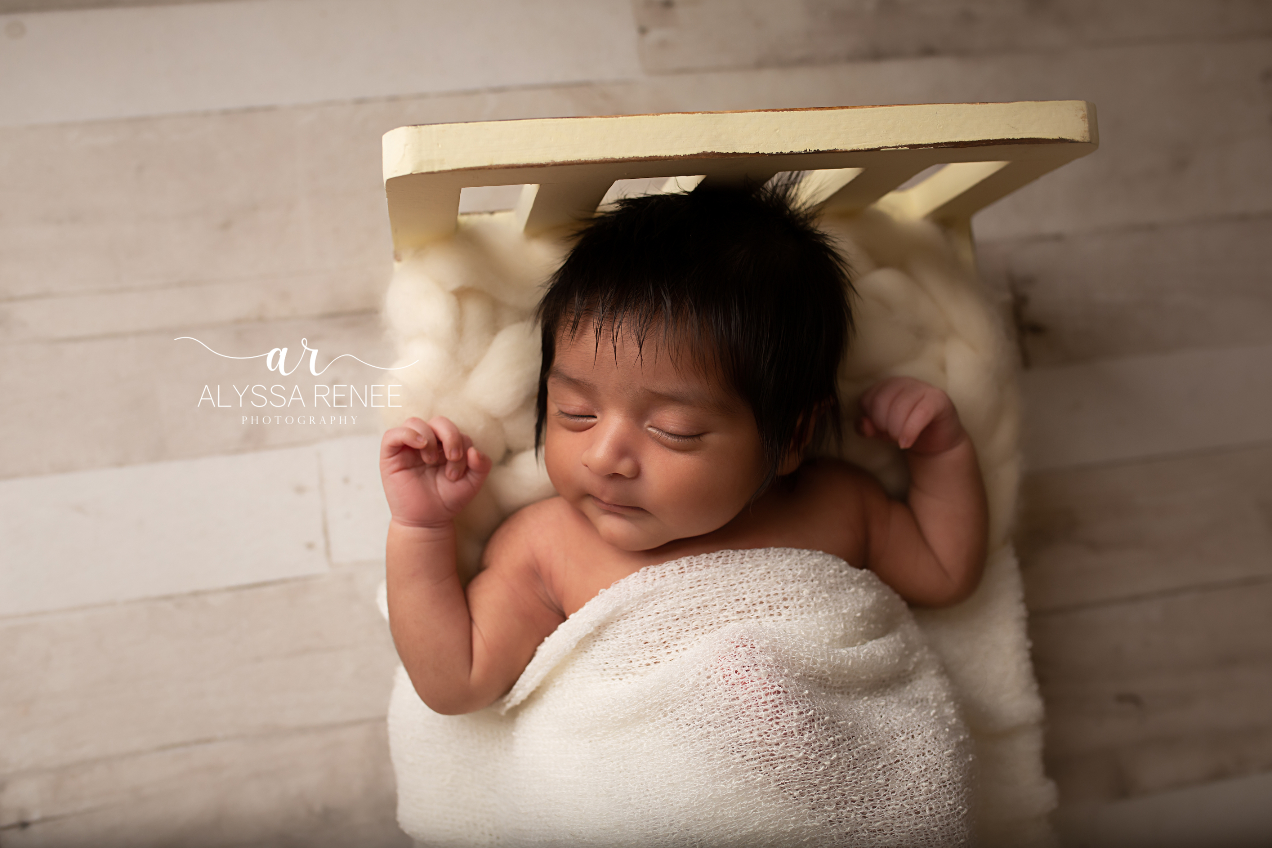 newborn portrait of baby in crib with handmade blanket prop