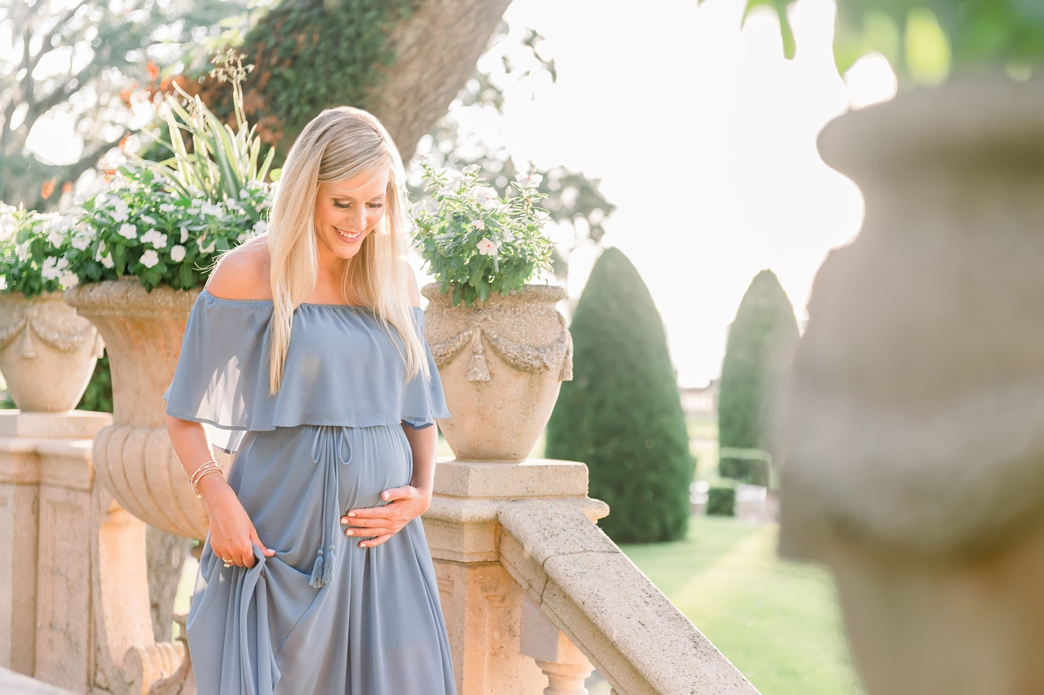 pregnant mother to be with long blonde hair, she is wearing a strapless light blue gown, beautiful manicured garden grounds